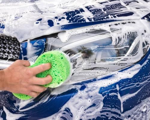 man-washing-a-soapy-blue-car-with-a-green-sponge-picture-id1148160621